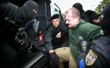 Kotleba arresteras av maskerad polis efter sitt tal 2009.