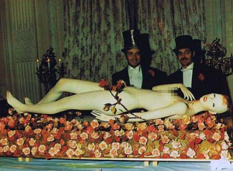 På ett bord låg en vit naken skyltdocka, som för en begravning omgiven av rosor.