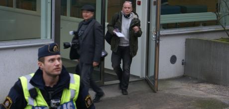 En polis med kamera på bröstet skyddar två journalister.