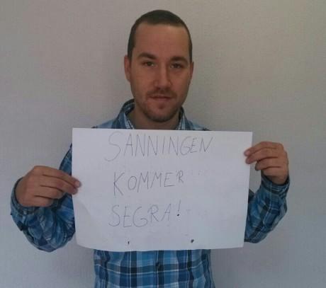 """Den efterlyste nationalisten Andreas Carlsson står och håller upp ett med texten """"Sanningen skall segra!""""."""
