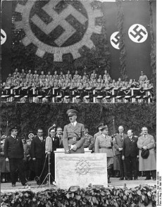 Adolf Hitler lägger grundstenen till Volkswagenverk den 26 maj 1938. Längst till höger i bilden syns Ferdinand Porsche.