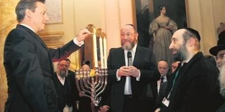 David Cameron, som leder Storbritanniens regering, är snabb att gå sionisternas ärenden. Här ses han delta i judiska ritualer.