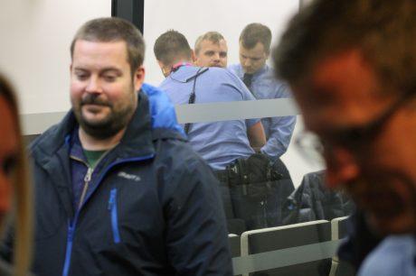 Den politiska fången Martin Saxlind skymtas bakom säkerhetsglas.